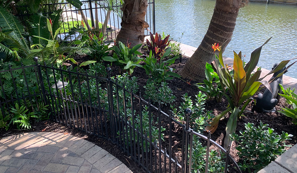 Custom designed and installed landscaping next to a canal in Bird Key, FL