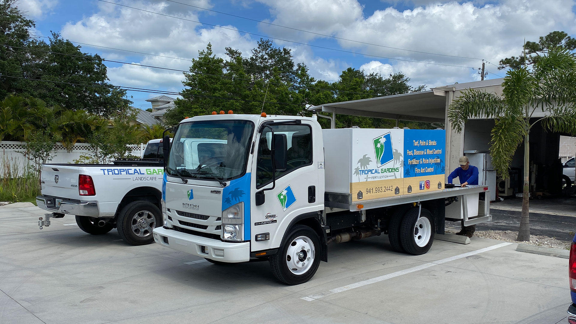 Tropical Gardens Landscape fertilizer truck and maintenance truck parked in front of our building in Sarasota, FL.