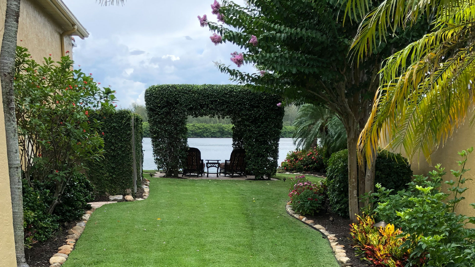 An ornamental shrub trimmed into an archway in the lawn next to a lake.