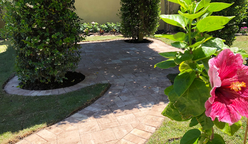 Custom designed paver patio with a walkway and new landscaping in the backyard of an Longboat Key, FL home.